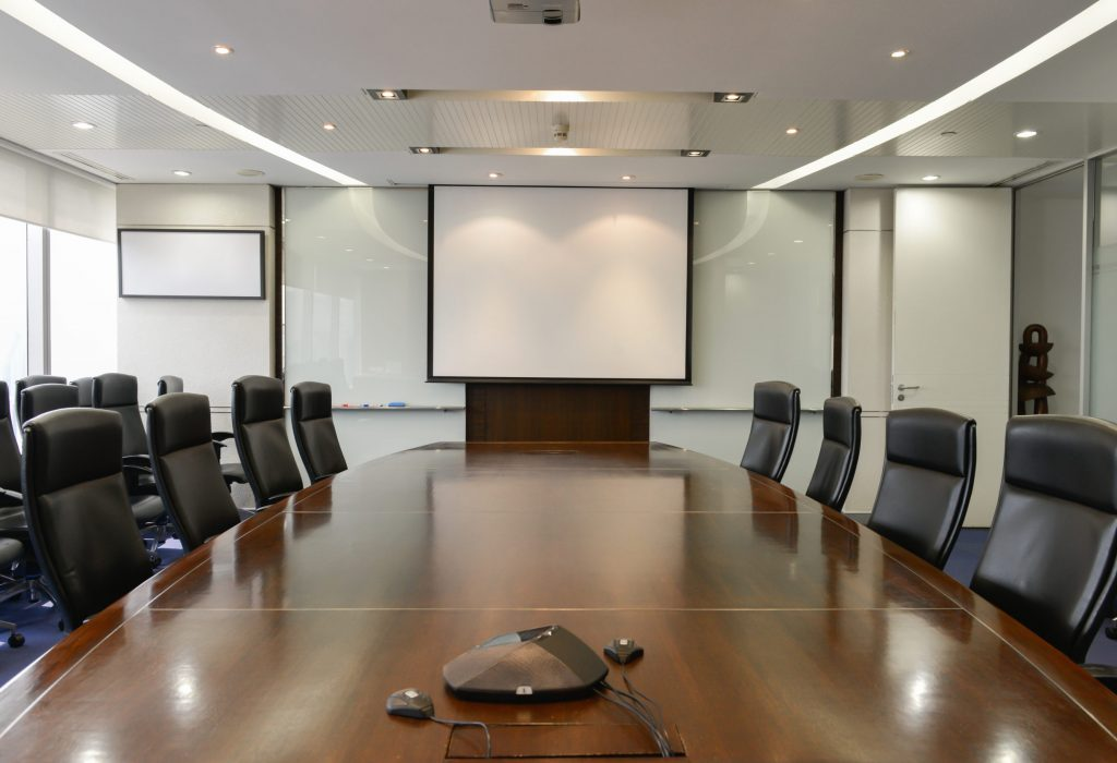 Business board room with white projector screen and IP Phone